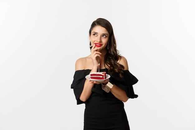 Koncepcja uroczystości i partii. marzycielska kobieta w czarnej sukni, życząc, myśląc i trzymając tort urodzinowy ze świecą, stojąc na białym tle.