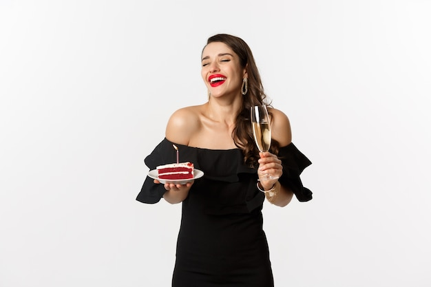Koncepcja uroczystości i partii. modna kobieta trzyma tort urodzinowy ze świecą i pije szampana, śmiejąc się szczęśliwy, stojąc na białym tle.
