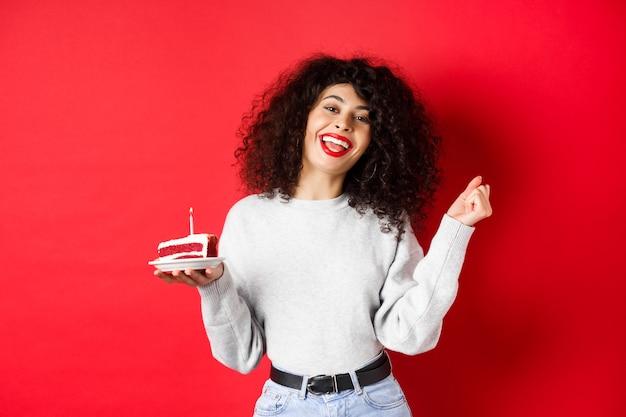 Koncepcja uroczystości i wakacji. szczęśliwa piękna kobieta tańczy i robi życzenia urodzinowe, trzymając tort urodzinowy i uśmiechnięta, stojąca na czerwonym tle.