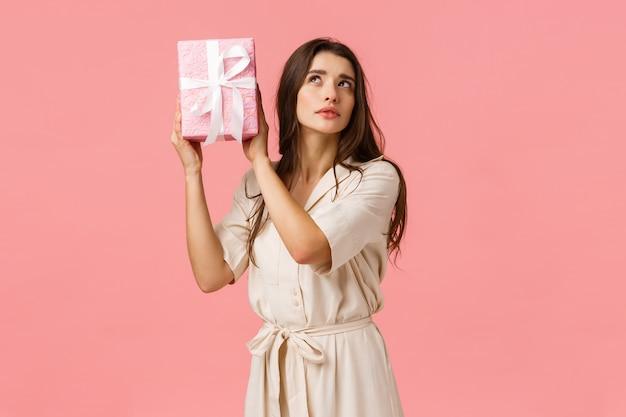 Koncepcja uroczystości, kobiety i oczekiwania. powabna ciekawa młoda kobieta drżąca pudełko z zainteresowaniem, skupiona, zaintrygowana tym, co w środku, stojąca różowa ściana, otrzyma prezent