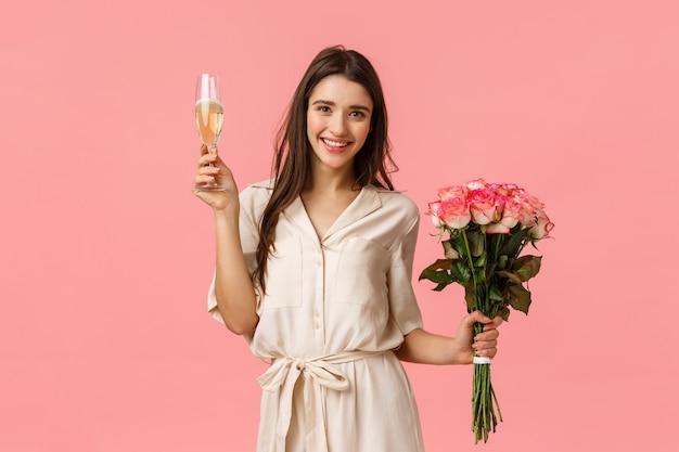 Koncepcja uroczystości, radości i urody. piękna młoda czuła kobieta w sukni, trzyma bukiet kwiatów, podnosi szklanego szampana, daje grzance, uśmiecha się i cieszy się przyjęcia, menchii ściana