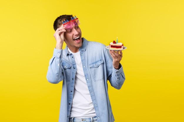 Koncepcja uroczystości, święta i ludzie emocje. podekscytowany szczęśliwy urodzinowy facet, zdejmowane okulary przeciwsłoneczne i zdumiony pyszny tort urodzinowy z jedną świeczką, żółte tło.