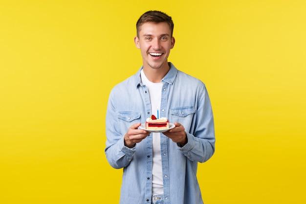 Koncepcja uroczystości, święta i ludzie emocje. radosny przystojny młody człowiek o przyjęcie urodzinowe, trzymając tort urodzinowy ze świecą i uśmiechając się, życząc na żółtym tle.