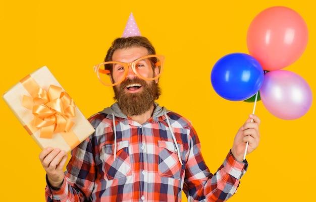 Koncepcja uroczystości. uśmiechnięty mężczyzna z teraźniejszości pudełkiem i balonami. wszystkiego najlepszego z okazji urodzin. święta i imprezy.