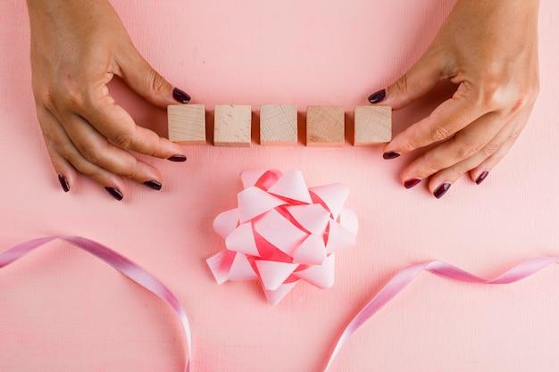 Koncepcja uroczystości z kokardą, wstążką na różowym stole leżał płasko. kobieta trzyma drewniane kostki.