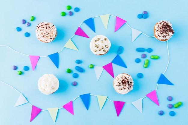 Koncepcja urodzinowa z posypką; cukierki i trznadel na niebieskim tle