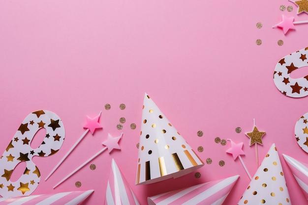Koncepcja urodziny. imprezowe czapki, maski i świeczki urodzinowe na różowym tle. widok z góry na dół z miejscem na kopię