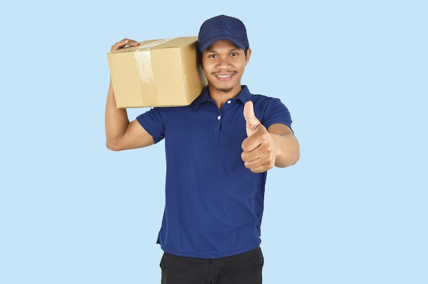 Koncepcja usługi dostawy mężczyzna dostawy trzyma pudełko i kciuki do góry na niebieskim tle