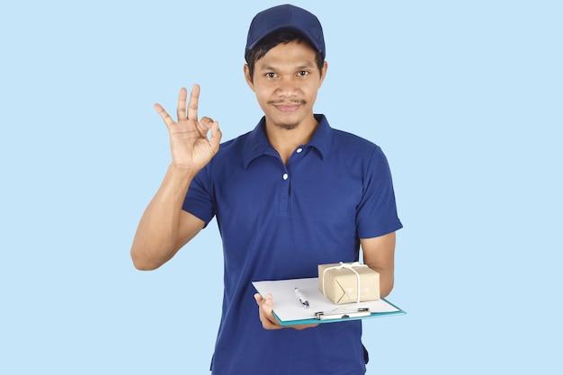 Koncepcja usługi dostawy mężczyzna dostawy trzymający schowek w pudełku i pokazujący ok na niebiesko