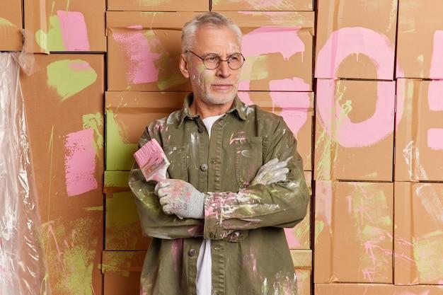 Koncepcja usługi remontu i malowania domu. poważny brodacz krzyżuje ramiona i patrzy zamyślony na bok trzyma pędzel nosi rękawiczki, a brudna koszula pęka podczas naprawy. zamyślony dekorator