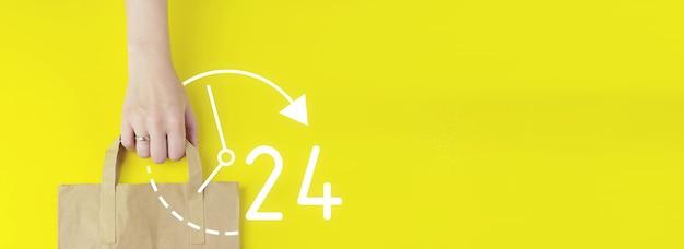 Koncepcja usługi w pełnym wymiarze godzin. torba na zakupy z brązowego papieru z recyklingu w ręku z hologramem 24 7 przez cały dzień przez całą noc ikona na żółtym tle, płasko leżał. koncepcja sprzedaży letniej. koncepcja usługi dostawy