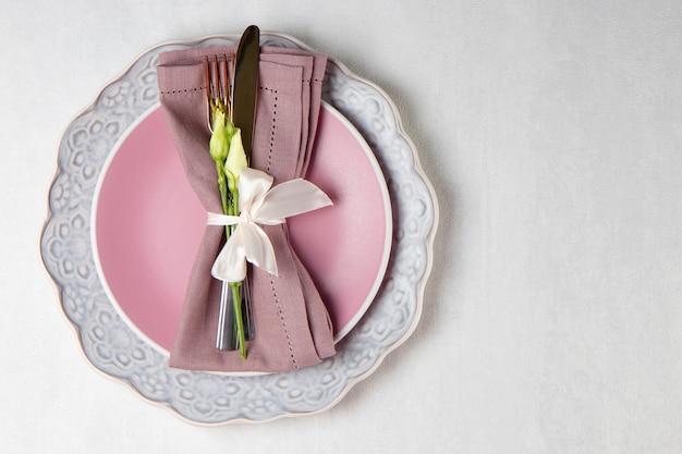 Koncepcja ustawienia stołu weselnego różowy talerz sztućców na lnianej serwetce i kwiaty na białym