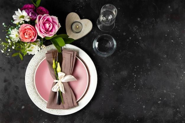 Koncepcja ustawienia stołu weselnego. talerz, sztućce na lnianej serwetce i kwiatach, widok z góry, zdjęcie z copyspace.
