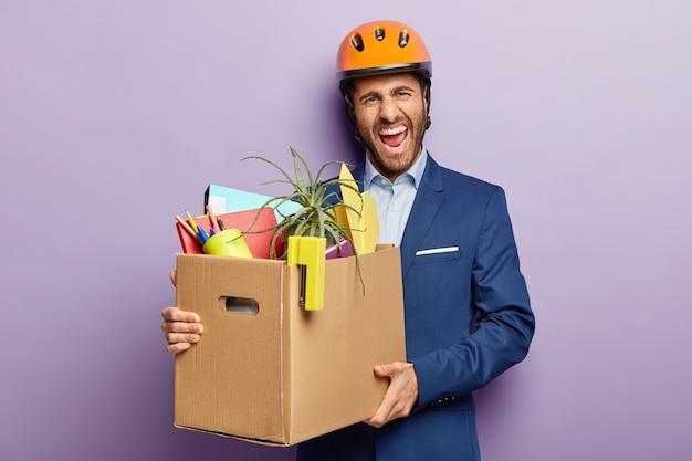 Koncepcja utraty pracy. zirytowany inżynier zwolniony z pracy, niesie kartonowe pudełko z osobistymi rzeczami biurowymi, uśmiechnięta twarz