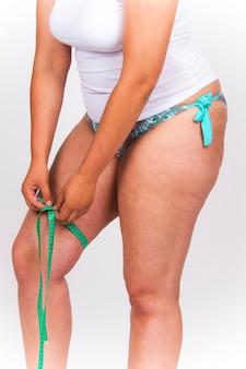 Koncepcja utraty wagi. rozmiar prawdziwego człowieka plus modelka mierząca uda, trzymająca krawiecką miarkę.