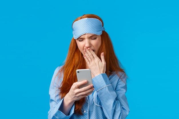 Koncepcja uzależnienia, stylu życia i urody gadżetów. urocza ruda dziewczyna idzie spać i przewija telefon, ziewanie mruży uczucie zmęczenia, ubrana w piżamę i maskę do spania, niebieska ściana
