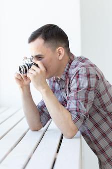 Koncepcja vintage, fotograf i ludzie - przystojny mężczyzna z aparatem retro na białej powierzchni z miejsca na kopię