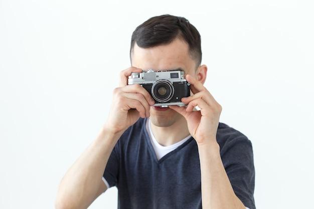 Koncepcja vintage, fotograf i ludzie - przystojny mężczyzna z aparatem retro na białej powierzchni z miejsca na kopię.