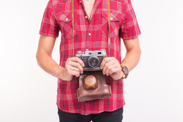 Koncepcja vintage, fotograf i ludzie - retro aparat w rękach mężczyzny na białym tle.