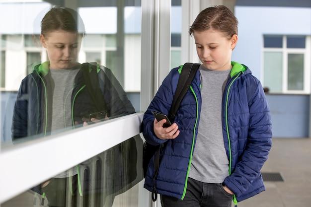 Koncepcja wagary, młody chłopak trzymający się z dala od szkoły i grający w gry na telefonie komórkowym, nieobecność w szkole