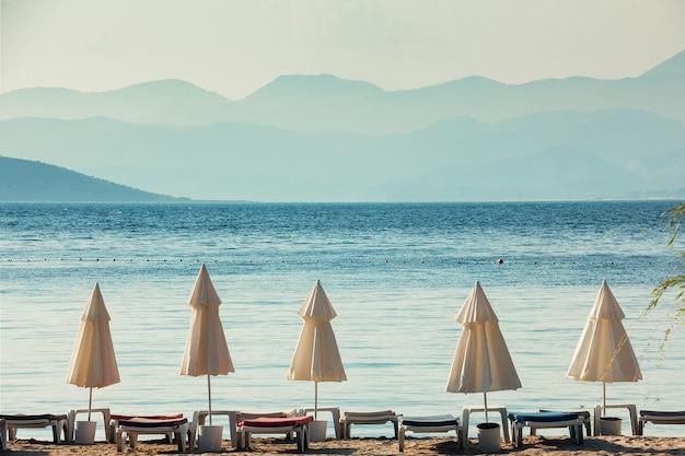 Koncepcja wakacje, białe parasole, błękitne morze i duże góry na horyzoncie