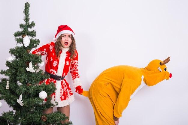 Koncepcja wakacje, boże narodzenie i żart - para w stroju świątecznym, wygłupiać się razem na białym tle