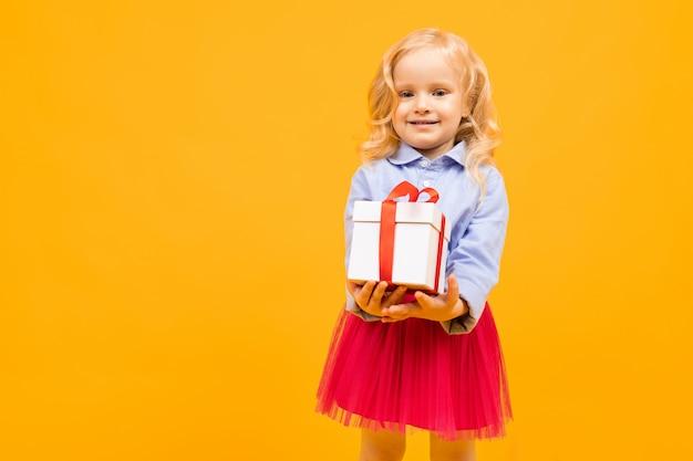 Koncepcja wakacje. mała dziewczynka z prezentem na jasnym żółtym tle
