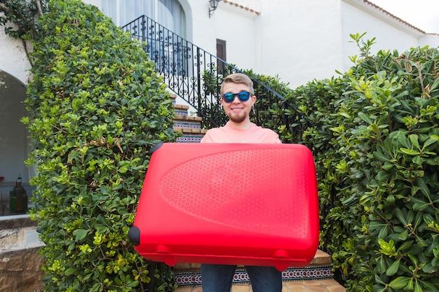 Koncepcja wakacje, podróże i turystyka. przystojny mężczyzna stojący na schodach z czerwoną walizką.