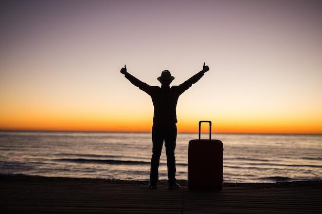 Koncepcja wakacje, wakacje i podróże - sylwetka młodego człowieka z walizką na plaży o wschodzie słońca.