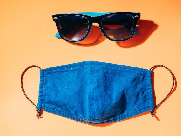 Koncepcja wakacji i podróży w warunkach pandemii covid-19. okulary i maska na pomarańczowym stole. leżał płasko, kopia przestrzeń.