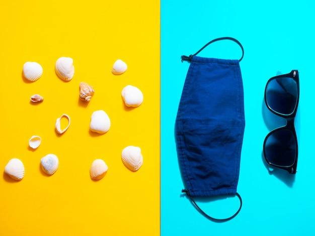 Koncepcja wakacji i podróży w warunkach pandemii covid-19. okulary, muszle i maska na żółtym i niebieskim stole. leżał płasko, kopia przestrzeń.