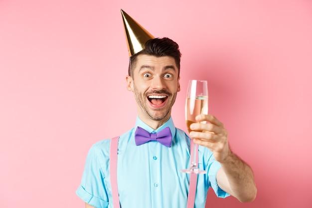 Koncepcja wakacji i uroczystości. podekscytowany urodzinowy facet podnoszący kieliszek szampana, wznoszący toast lub przemówienie, stojący w czapce i bawiący się na różowym tle.