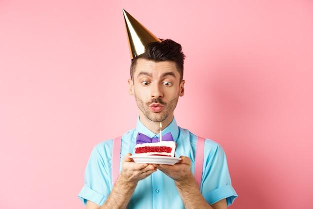 Koncepcja wakacji i uroczystości. szczęśliwy młody człowiek w kapeluszu przyjęcie urodzinowe dmuchanie świeczką na torcie, życząc życzenia na b-day, stojąc na różowym tle.