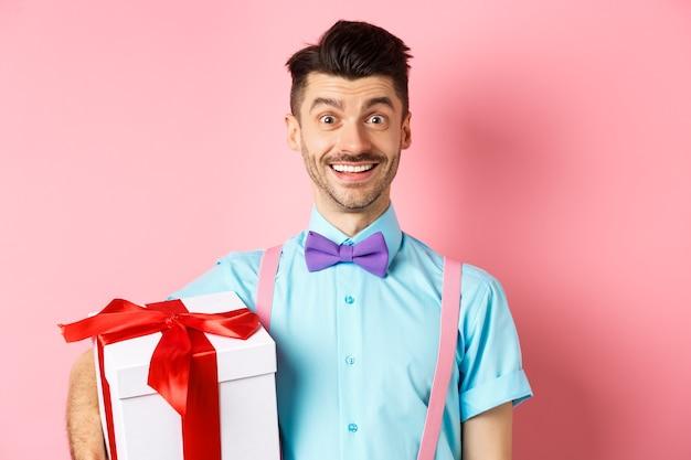 Koncepcja wakacji i uroczystości. wesoły facet w muszce i na szelkach przynosi na imprezę pudełko prezentowe, trzymając prezent i uśmiechnięty, stojąc na różowym tle.