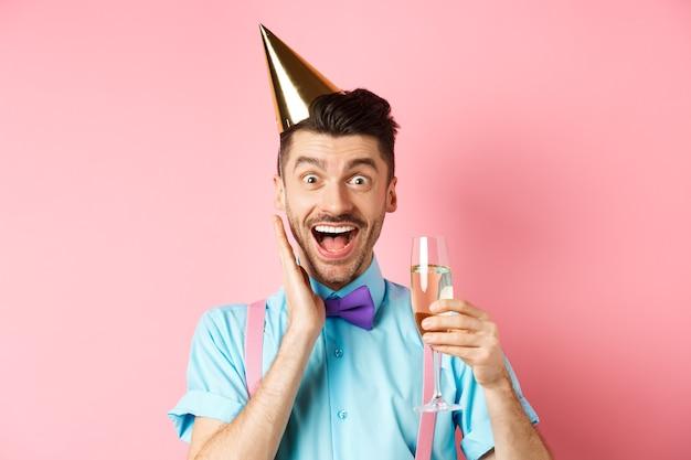Koncepcja wakacji i uroczystości. zabawny młody człowiek w urodzinowej czapce świętuje, krzyczy z radości i zaskoczenia, podnosi kieliszek szampana i uśmiecha się, stojąc na różowym tle.