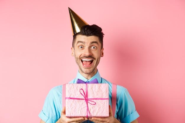 Koncepcja wakacji i uroczystości. zbliżenie szczęśliwego faceta w kapeluszu imprezowym otrzymuje prezent urodzinowy, krzyk radości i wiwatu, stojący na różowym tle.