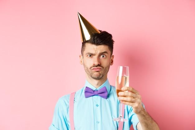Koncepcja wakacji i uroczystości. zmartwiony młody człowiek w imprezowej czapce, marszczący brwi z powątpiewającą miną, unoszący zdziwiony kieliszek szampana, stojący na różowym tle.