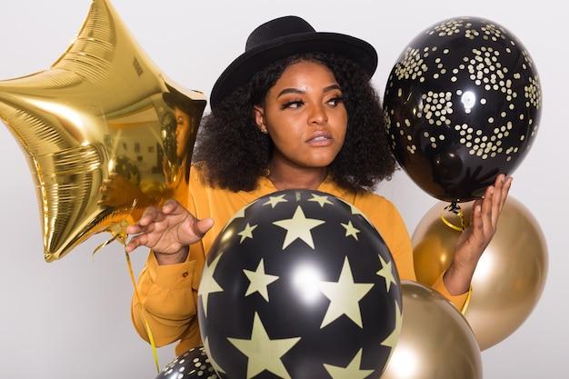 Koncepcja wakacji, imprez i zabawy. portret uśmiechnięta młoda african-american młoda kobieta z balonów strony na białym tle