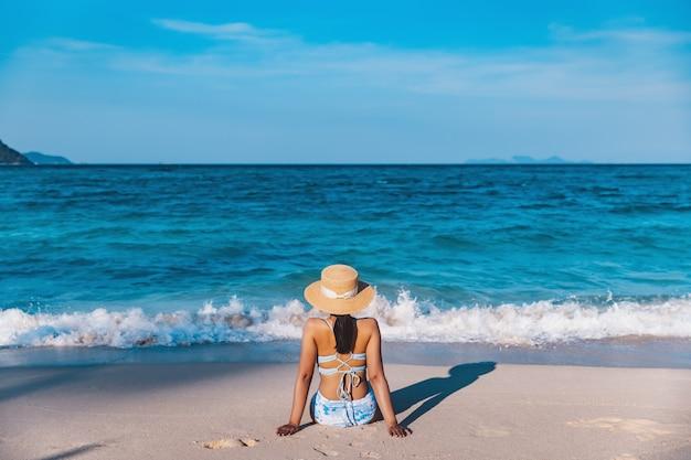 Koncepcja wakacji letnich podróży, podróżnik azjatycka kobieta z bikini i kapelusz relaks na plaży w dzień w koh lipe, satun, tajlandia
