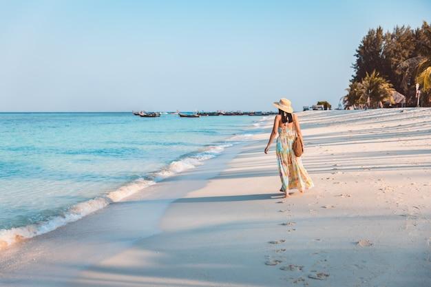 Koncepcja wakacji letnich podróży, szczęśliwy podróżnik asian kobieta z sukienka relaks i zwiedzanie na plaży wieczorem w koh lipe, satun, tajlandia