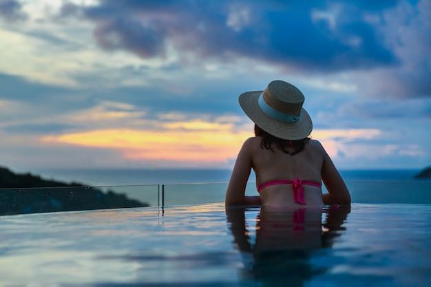 Koncepcja wakacji letnich podróży, szczęśliwy podróżnik azjatycka kobieta z kapeluszem i bikini relaks w luksusowym hotelu z basenem bez krawędzi