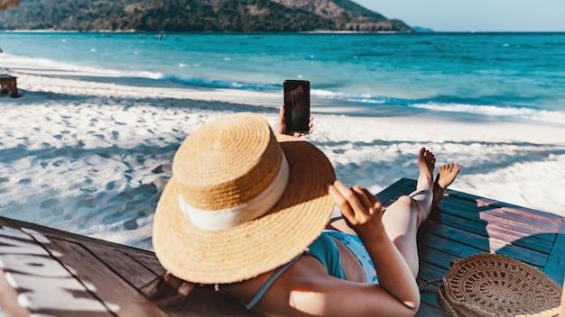 Koncepcja wakacji letnich podróży, szczęśliwy podróżnik azjatycka kobieta za pomocą telefonu komórkowego i zrelaksować się na plaży krzesła w koh lipe, satun, tajlandia