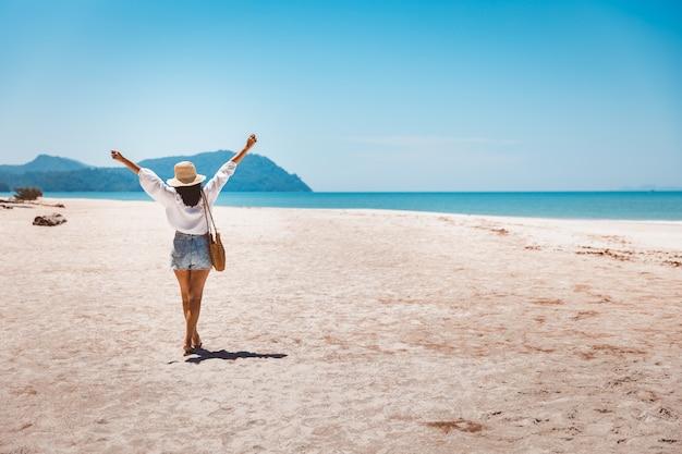 Koncepcja wakacji letnich podróży, szczęśliwy podróżnik azjatykcia kobieta relaks i zwiedzanie na plaży wieczorem w koh lipe, satun, tajlandia