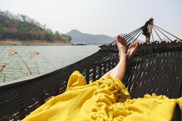 Koncepcja wakacji letnich, szczęśliwa samotna podróżniczka azjatycka kobieta z żółtą sukienką relaksuje się w hamaku nad jeziorem w tamy srinakarin, kanchanaburi, tajlandia, noga zbliżenie