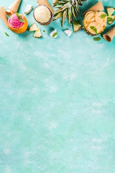 Koncepcja wakacji letnich, zestaw różnych sorbetów z lodami tropikalnymi, mrożone soki w ananasie, grejpfruta i kokosie, jasnoniebieski beton
