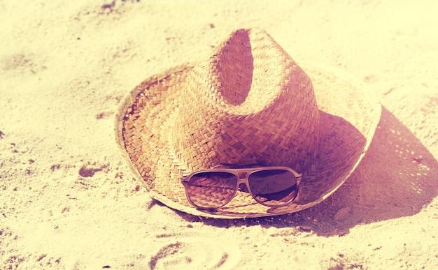Koncepcja wakacji lub urlopu. piękne okulary słoneczne z straw hat na piasku. plaża. styl życia.