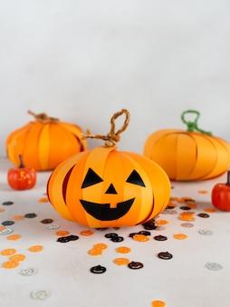 Koncepcja wakacji na halloween z dekoracjami papierowymi dyniami i kompozycją konfetti