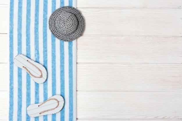 Koncepcja wakacji na plaży. japonki plażowe, bawełniany ręcznik w paski, szara czapka od słońca. letnie mieszkanie leżało