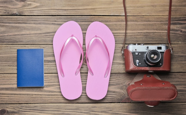 Koncepcja wakacji na plaży, turystyka. tło podróżnik lato. japonki, aparat retro, paszport na podłoże drewniane.