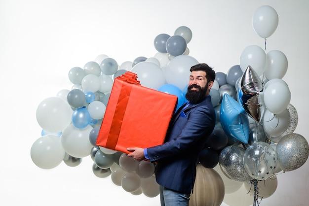 Koncepcja wakacji na prezent urodzinowy brodaty mężczyzna z balonami z helem trzyma duże pudełko na prezent urodzinowy